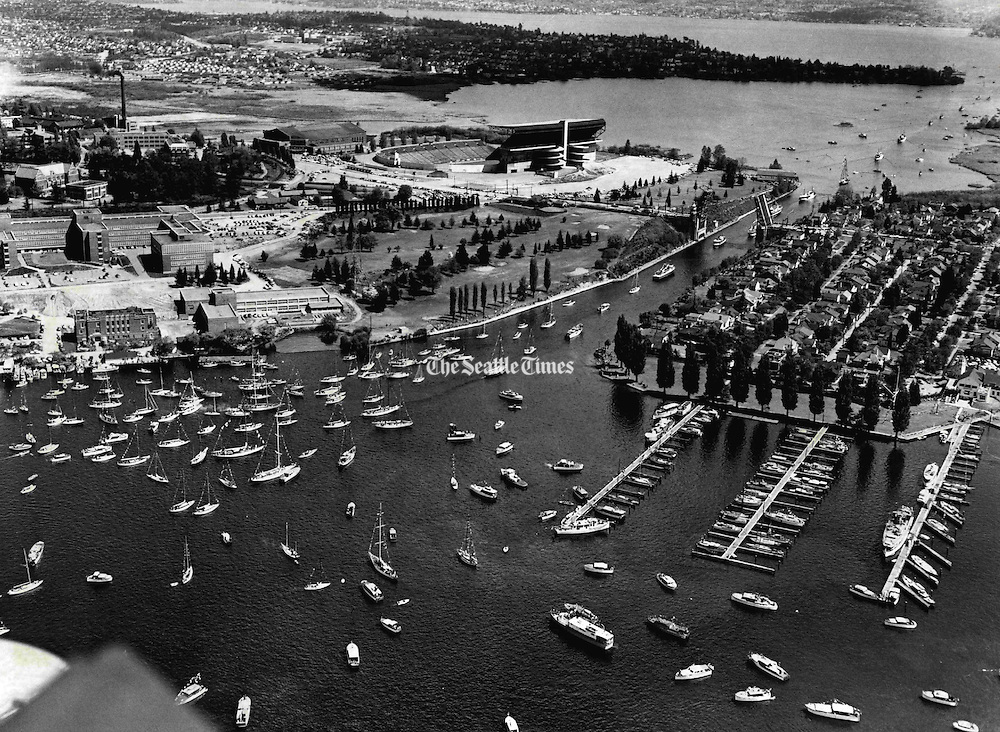 More than 800 sailboats and power craft paraded through the Montlake Cut to Lake Washington in the Seattle Yacht Club's Opening Day Regatta. This aerial photograph shows sailboats forming for the parade. The Seattle Yacht Club moorages on Portage Bay are at lower right. (Josef Scaylea / The Seattle Times, 1952)