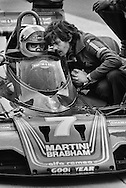 Martini-Brabham race driver John Watson works with Brabham designer Gordon Murray,  during practice for the 1979 United States Grand Prix at Watkins Glen. Watson would qualify second, but, with a light drizzle for the race, the team ordered Watson to start on Goodyear dry racing &quot;slicks&quot; on the chance that the track might dry and Watson would have a distinct advantage. The rain continued until the final  few laps. Watson would finish 12th.<br /> <br /> While 1977 Formula One cars remained the fastest, most agile racing machines in the world, team race strategies, especially for rain were limited, due to slow tire changes, rules outlawing refueling and lack of car-to-pit communications. They could go with the field or gamble. Thus, Brabham's choice to put Watson on dry tires wasn&rsquo;t all about the car, but the driver&hellip;a Formula 1 driver&hellip;and what he could do with this uncoordinated collection of metal, power and dynamics.<br /> <br /> In those days, teams counted on their drivers to use their tremendous reflexes, their accumulated knowledge and the best guesses of their engineer to stay on the track regardless of the conditions. <br /> <br /> Their sole task was to race what they were given; to carry the car on their backs and push it out to the edge of control and beyond&hellip;and get points. Sometimes they succeeded, sometimes they didn&rsquo;t. And if they didn&rsquo;t they were gone, or worse.<br /> <br /> Watson would go on to have a 12-year career, scoring three wins and finishing 3rd in the 1982 World Championship standings.