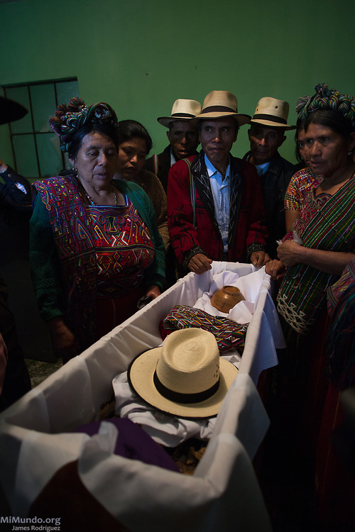 Family members watch as the remains of Diego Solis Lopez, killed in 1982, are arranged inside a coffin. The human remains of Solis Lopez and 35 other Ixil Mayan war victims were returned to their surviving family members for a proper burial. Most of the victims, exhumed from mass graves in the Xe'xuxcap area of Acul, Nebaj, starved in the mountainside while fleeing State-led repression in 1982. The remains were exhumed by members of the Forensic Anthropology Foundation of Guatemala (FAFG) in 2013 and after DNA analysis, most remains were identified and buried 35 years after their death. Nebaj, Quiché, Guatemala. February 2, 2017.