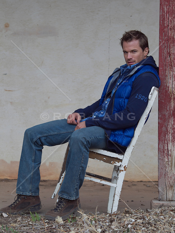 good looking man in a chair leaning back against a post