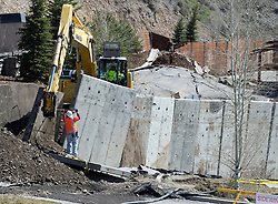 Workers repurpose a concrete wall, originally meant to reinforce the slope, into the foundation of a new access road as the landslide around Budge Drive continues slowly downhill on Friday. The bulging pavement of the Walgreens parking can be seen in the background.