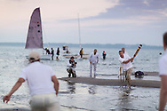 Action during the annual Brambles cricket match between members of the Island Sailing Club and the Royal Southern Yacht Club on the Bramble Bank in the centre of The Solent. The teams from Hamble, Hampshire and Cowes, Isle of Wight play their eccentric competition in the middle of the busy shipping lane in a tradition dating back to the 1950's. The teams take it in turns to win in alternate years. This year the ISC won and hosted breakfast following the game which commenced at 06:30am.<br /> Picture date: Thursday 11th September, 2014.<br /> Picture by Christopher Ison. Contact +447544 044177 chris@christopherison.com