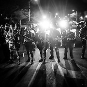BALTIMORE, USA - APRIL 29: Police in riot gear prepare to enforce the declared curfew at the intersection of West North Avenue and Pennsylvania Avenue in Baltimore, USA on April 29, 2015. Protests following the death of Freddie Gray from injuries suffered while in police custody have turned violent with people throwing debris at police and media and burning cars and businesses.