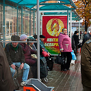 "A bus shelter poster proclaims ""Belarus Blooms"" while glum passengers wait for public transportation in Minsk on Oct. 22, 2009."