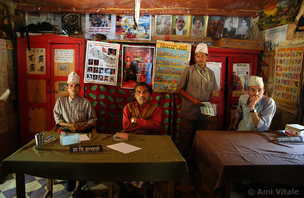 """RUKUM DISTRICT, NEPAL, APRIL 16, 2004:  Maoist teachers sits in a government school underneath posters of the Royal Nepalese family in Rukum District April 16, 2004. The Maoists intend to close the government schools and establish their own educational system. Analysts and diplomats estimate there about 15,000-20,000 hard-core Maoist fighters, including many women, backed by 50,000 """"militia"""".  In their remote strongholds, they collect taxes and have set up civil administrations, and people's courts. They also raise money by taxing villagers and foreign trekkers.  They are tough in Nepal's rugged terrain, full of thick forests and deep ravines and the 150,000 government soldiers are not enough to combat this growing movement that models itself after the Shining Path of Peru. (Ami Vitale/Getty Images)"""