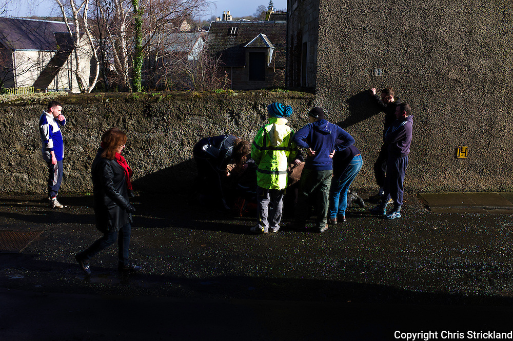 Jedburgh, Scottish Borders, UK, 26th February 2015 - The annual game of hand ba' takes place every year the Thursday after Fastern's E'en. The ba' is said to represent an Englishman's head, and the ribbons his hair, claimed after a battle in which the Scots regained nearby Ferniehirst Castle in 1548. The head was used in a celebratory kickabout. Those born south of the towns Market Cross play for the 'Uppies' scoring at the Castle Jail, conversely those born North play for the Doonies, scoring near the River Jed. The knack of the game is to smuggle the ball through team members, through any means possible, there are no rules as such.