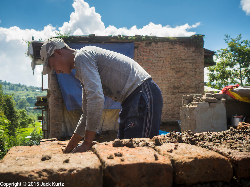 03 AUGUST 2015 - SANKHU, NEPAL: A man repairs a home destroyed by the earthquake in Sankhu, a community about 90 minutes from central Kathmandu. He is using bricks recycled from the original home and mud from the earthquake rubble as mortar.  The Nepal Earthquake on April 25, 2015, (also known as the Gorkha earthquake) killed more than 9,000 people and injured more than 23,000. It had a magnitude of 7.8. The epicenter was east of the district of Lamjung, and its hypocenter was at a depth of approximately 15km (9.3mi). It was the worst natural disaster to strike Nepal since the 1934 Nepal–Bihar earthquake. The earthquake triggered an avalanche on Mount Everest, killing at least 19. The earthquake also set off an avalanche in the Langtang valley, where 250 people were reported missing. Hundreds of thousands of people were made homeless with entire villages flattened across many districts of the country. Centuries-old buildings were destroyed at UNESCO World Heritage sites in the Kathmandu Valley, including some at the Kathmandu Durbar Square, the Patan Durbar Squar, the Bhaktapur Durbar Square, the Changu Narayan Temple and the Swayambhunath Stupa. Geophysicists and other experts had warned for decades that Nepal was vulnerable to a deadly earthquake, particularly because of its geology, urbanization, and architecture.    PHOTO BY JACK KURTZ