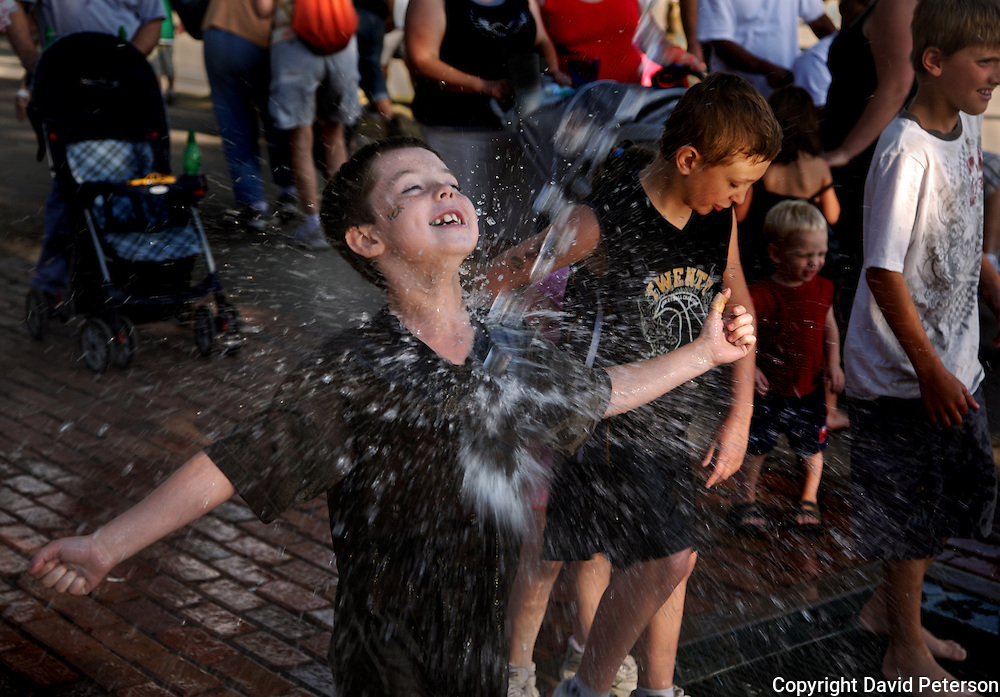 The spray from a fountain cools off Garrett Krumrey, from Des Moines, Iowa, at the 2008 Iowa State Fair, held annually in his home town.  Krumrey and his family were part of a record crowd at this year's fair.