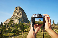 Close up the of Fujifilm X-T10 digital camera while taking pictures of Devil's Tower in Wyoming.