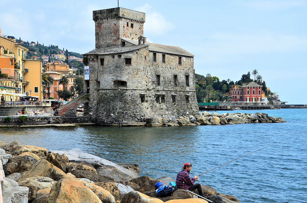 Fisherman Along Harbor in Rapallo, Italy <br /> Rapallo is a lovely northern Italian resort town along the Ligurian Sea and a short drive from Genoa.  It is blessed with moderate, year-round weather, a picturesque harbor, historic sites, excellent shopping and seafood restaurants plus one of Italy&rsquo;s oldest golf courses.  Or you can just sit along the rocks, cast out your fishing line and enjoy the view.