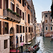 """Gondolas are traditional, flat-bottomed rowing boats which ferry people through Venetian canals. From a peak of 10,000 gondolas 200 years ago, just 500 gondolas now serve Venice. The banana-shaped modern gondola was developed in the 1800s. The left side of the gondola is made longer than the right side to resist leftwards drift at the forward stroke. The gondolier stands on the stern facing the bow and rows just on the right side, with a forward stroke and compensating backward stroke. The oar or rèmo is held in an oar lock, or fórcola, shaped for several rowing positions. The decorative fèrro (meaning iron) ornament on the front can be made of brass, stainless steel, or aluminum, as counterweight for the gondolier standing near the stern. The six horizontal lines and curved top of the ferro represent Venice's six sestieri (districts) and the Doge's cap. Painting gondolas black originated as a sumptuary law banning ostentatious competition between nobles. Until the early 1900s, many gondolas had a small cabin (felze) with windows which could be closed with louvered shutters--the original """"venetian blinds."""" The romantic """"City of Canals"""" stretches across 117 small islands in the marshy Venetian Lagoon along the Adriatic Sea in northeast Italy, Europe. Venice and the Venetian Lagoons are honored on UNESCO's World Heritage List."""