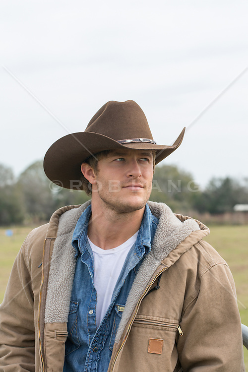 handsome cowboy sitting on a fence at a ranch portrait of an All American cowboy outdoors