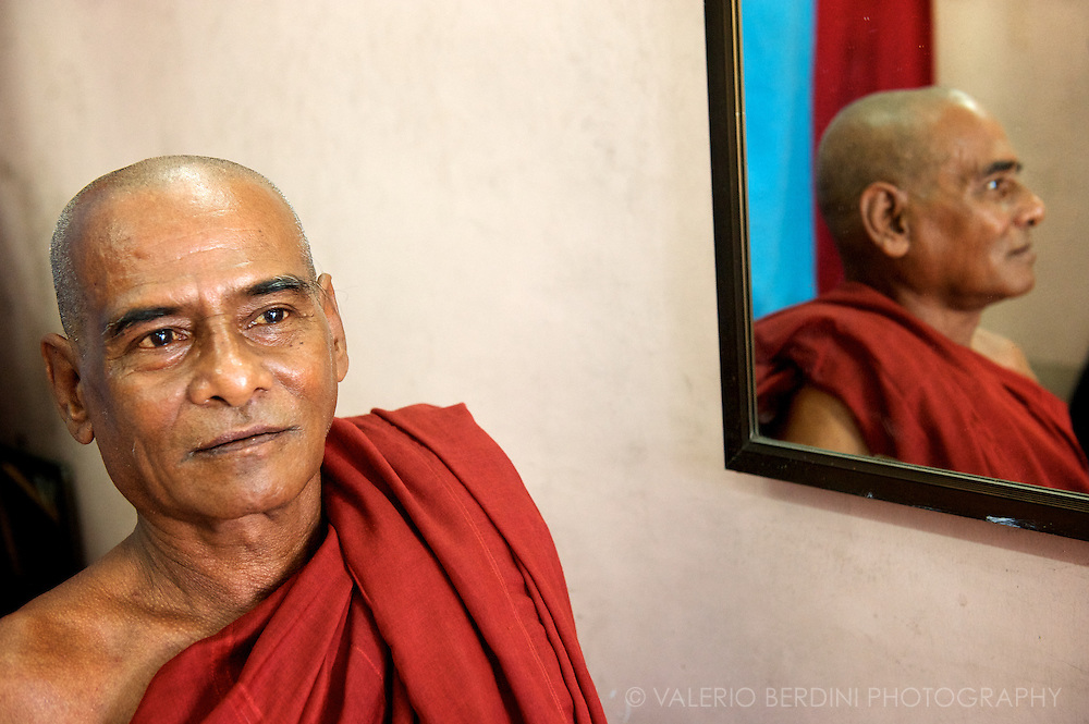 Bhikkhu poses for a portrait next to a mirror in one of the photographer's shops surrounding Sule pagoda in Rangoon.