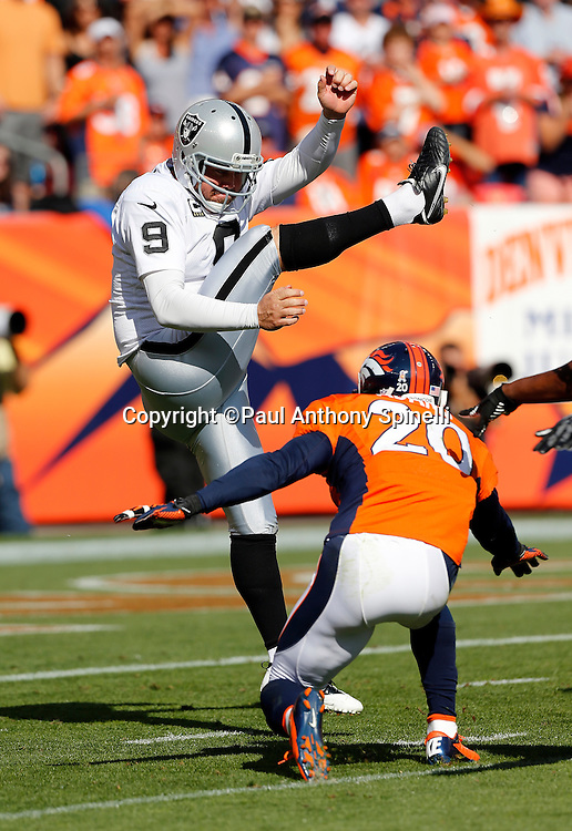 Oakland Raiders punter Shane Lechler (9) punts despite a near block by Denver Broncos strong safety Mike Adams (20) during the NFL week 4 football game on Sunday, Sept. 30, 2012 in Denver. The Broncos won the game 37-6. ©Paul Anthony Spinelli