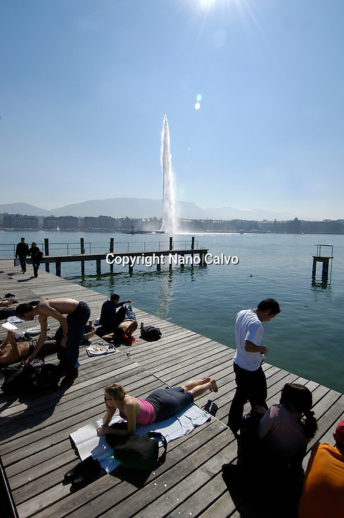 View of Jet Deau and people sunbathing in Bains des Paquis, in Geneva, Switzerland