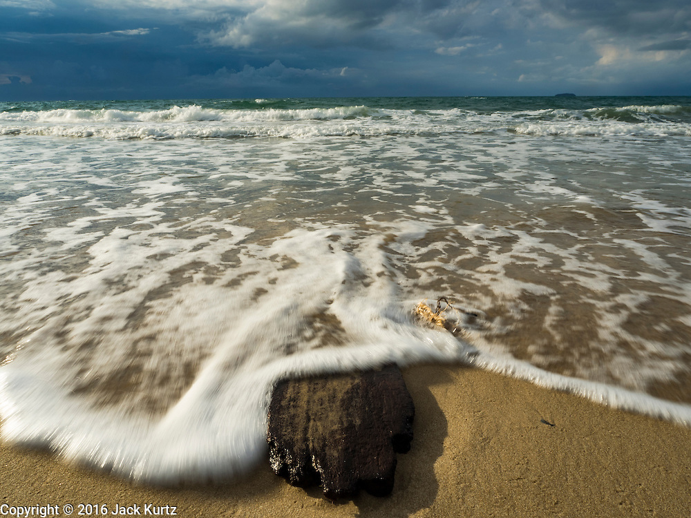 17 JANUARY 2016 - KLEANG, RAYONG, THAILAND:  Waves break over a piece of driftwood at Laem Mae Phim Beach and the Princess Beach Resort and Spa on the Gulf of Siam in Rayong province of Thailand.           PHOTO BY JACK KURTZ