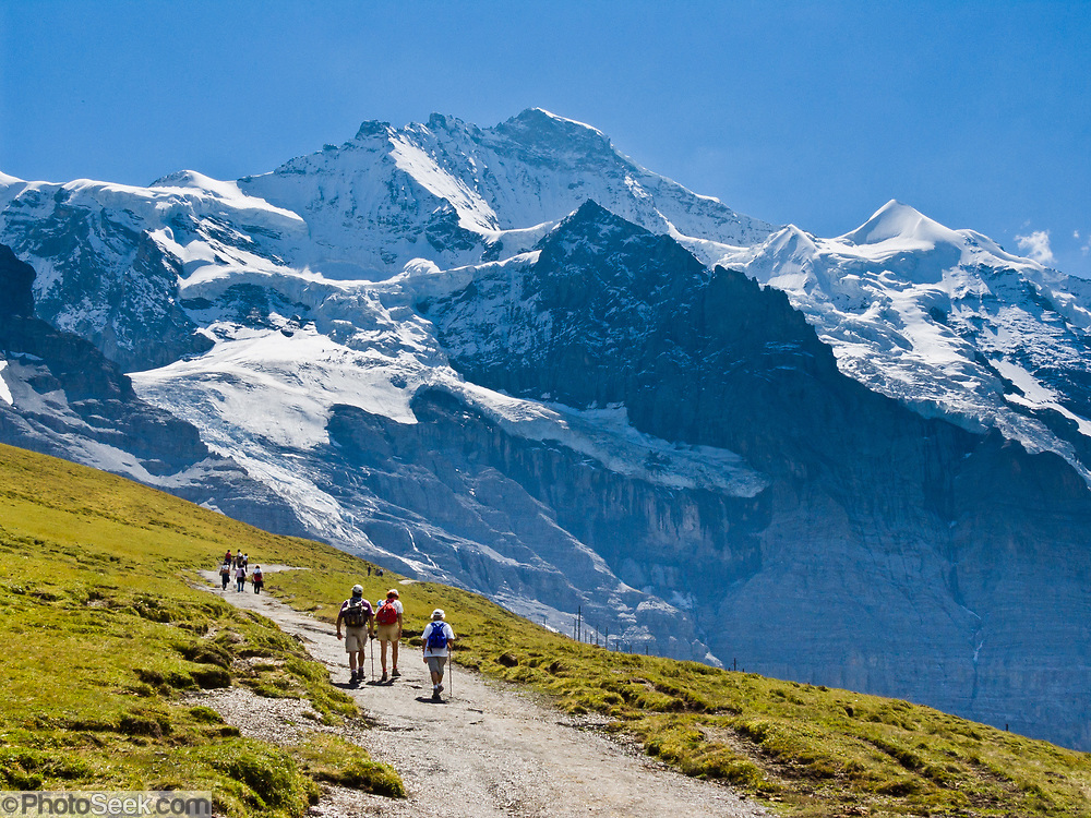 """Hike at Kleine Scheidegg towards the icy peak of Jungfrau (4158 meters or 13,642 feet) in the Berner Oberland, Switzerland, the Alps, Europe. The Bernese Highlands are the upper part of Bern Canton. UNESCO lists """"Swiss Alps Jungfrau-Aletsch"""" as a World Heritage Area (2001, 2007)."""