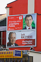 """two bill board posters for lech kaczynski party showing his face and red and white background in krakow poland. the writing reads """"lech kaczynski - silny prezydent uczciwa polska"""""""