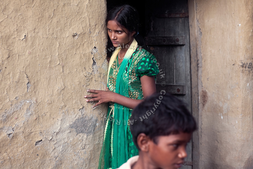 Kanchan Kumari Sharma, 12, is standing by the entrance of her home in Sersiya Kekrahi village, Varanasi District, Uttar Pradesh, India. In 2012, Kanchan went with a friend to bring lunch to her father, around 2 km away from her home. On the way they met Rajesh (rapist) and Ashok, a friend of his. Both girls were picked up on the spot using an excuse. Ashok drove Kanchan's friend home, but Rajesh forced Kanchan to travel with him during six days and for hundreds of kilometres across different states. (Mirzapur / Chennai / Itarsi / Bhusawal) He raped her once behind the station in Itarsi. With great effort and some coincidence, the uncle of Kanchan managed to bring her back home. Although she was scared, she insisted on going to the police to file a case (FIR). She was kept at the police station for 12 days and threatened to prevent her from filing an official case. Ashok and Rajesh are from higher caste and wealthy families. While Rajesh spent 24 days in jail initially in summer 2012, he is now a free man while the trial is still going on. Kanchan's family is now struggling to put together 30.000 Indian Rupees (500 USD) to continue battling for justice in court.