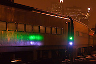 Rain soaked metal car sides reflect the white and green light from a switch stand in the middle of the Amtrak coach yard in Chicago, IL.