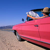 Old Route 66, Mojave Desert, Girl in  1962 Pink Cadillac Convertible reading map, California, USA