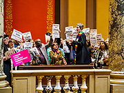 """04 MAY 2017 - ST. PAUL, MN: A Protestant minister reads bible passages supporting workers and women's rights in front of the Minnesota State Senate. About 200 people participated in a """"ISAIAH's 100 Days of Prophetic Resistance"""" rally at the Minnesota State Capitol in St. Paul. They represented churches from across the Twin Cities and were demonstrating in favor of paid sick leave, child care, and a higher minimum wage. The Twin Cities are more liberal than rural Minnesota and many Twin Cities municipalities have passed ordinances with paid sick leave, child care and higher minimum wages. Republican legislators from rural Minnesota have tried to pass laws in the legislature rolling back those ordinances.     PHOTO BY JACK KURTZ"""