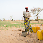 Raga Djibril at a well refurbished by WaterAid in the village of Gadirga in the Commune of Soukoukoutan in the Dosso Region of Niger on 23 July 2013. She says on most days she fetches a bucket of water in the morning and in the evening, topping up a supply she keeps in earthenware containers at her home. She says there are long queues for water in the dry season, but that during the rainy season (as when this photo was taken) it's easier to get water because villagers can use seasonal pools to water animals, do laundry and so on.