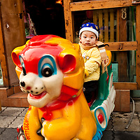 A young boy rides a mechanical tiger in the year of the Tiger