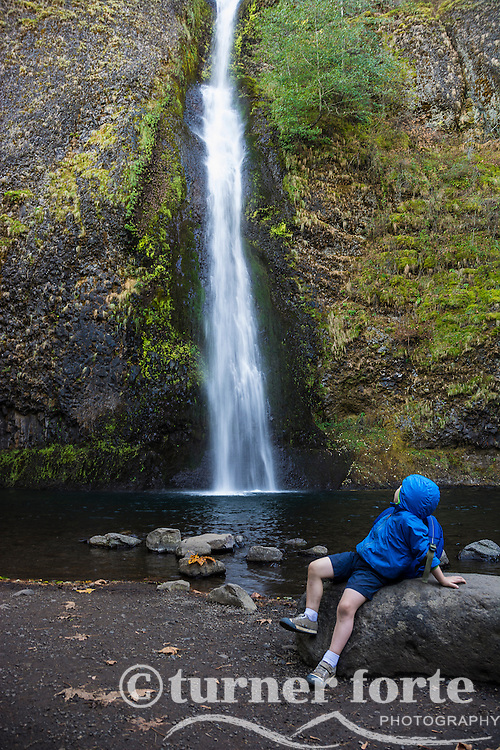 Toddler boy views Horsetail Falls and mossy canyon wall in autumn, Columbia Gorge, Oregon.