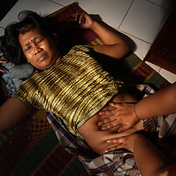 Suryani, 37, shows how she had a massage to get rid of her pregnancy in Jakarta, Indonesia, April 24, 2006. The woman demonstrating the technique is Marniati, 35, whose mother is a traditional birthing attendant, or TBA, and has performed many similar massages in their home. Over two million abortions are performed in Indonesia every year, many by unskilled practitioners. Thousands of women survive but often with life-long disabilities. It is said by doctors and activists that a woman dies every hour in Indonesia due to unsafe abortions.