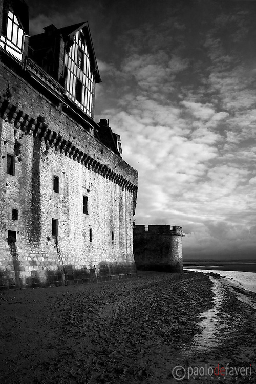 A view of the bastions and the northeast watchtower of the worldwide renowned medieval village of Mont Saint Michel in Normandy, France. The picture was taken on a early morning, few minutes before sunrise, while the rising tide was slowly entering the huge bay where the village lies.