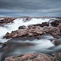 Canada, Nunavut Territory, Blurred image of rushing waterfall near Bury Cove along west coast of Hudson Bay 100 miles south of the Arctic Circle