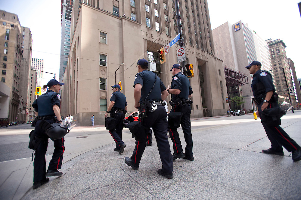 Police patrol the nearly deserted streets in the financial district of Toronto, Canada, June 25, 2010 where most office workers were told to work from home Friday as the city prepares to host the G20 leaders this weekend.<br /> AFP/GEOFF ROBINS/STR