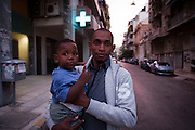 A immigrant poses for a portrait with his son in one of Athens' known immigrant neighbourhoods, Kato Patissia.