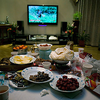 BEIJING, 25. JANUARY, 2009 :   Mr. Li's  sumptuous news years' setting in his apartment in Beijing .<br /> Mr. Li, a paper factory owner,  is facing one of his most difficult times .&quot; Last November the market suddenly went down ,&quot; Li says.   <br /> He had bought paper, a lot of paper, and paid 7000 Yuan/ t .<br />  Li's company buys paper from paper mills and lives from the sales to publishing houses and other companies.  Since the market's collapse , he manages to sell the paper only for 6000 Yuan/t.<br /> His clients' export business to the USA had shrunk in Southern China. Mobile phone manufacturers don't need paper for the instruction guides to their mobile phones anymore as their US clients buys less China- made mobile phones.<br />  Toy manufacturers don't need paper anymore  because Americans import less toys from China. &quot; The crisis has driven many of my clients into bancruptsy&quot;, says Li.<br />  <br /> China's Communist Party  which will celebrate its 60th anniversary in October, currently faces its biggest challenge since the beginning of the economic reforms 30 years ago  : &quot; The phase of  rapid economic growth is over. For the first time the government is threatened with a  mistrust of a wide section of the population&quot;, warns the Communist party's Shang Dewen in Beijing.   <br /> Not only the China's poorest worry about the furture, but as well China's middle class is concerned about the crisis.     1,5 Millionen university graduates didn't find a job until the end of 2008  and this summer there'll be an additional  6,1 Million new graduates. More than 12 percent of university graduates face unemployment in 2009.