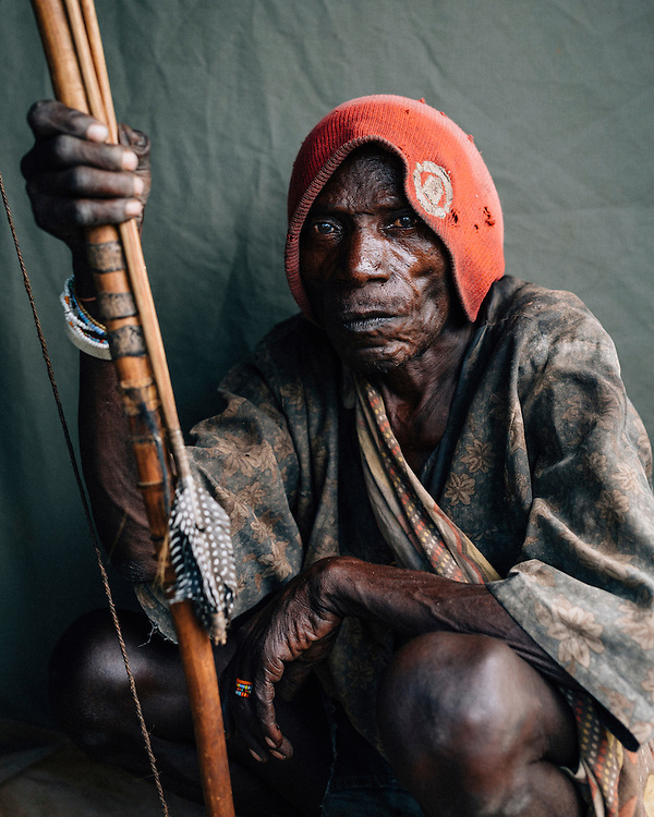Piwa, a septuagenarian of the Hazda tribe, poses for a photo with his bow and arrow. Piwa remembers how the Rhino roamed when he was younger, now they have mostly been hunted and poached to extinction. Yaeda valley, Northern Tanzania. Photo by Greg Funnell, March 2016