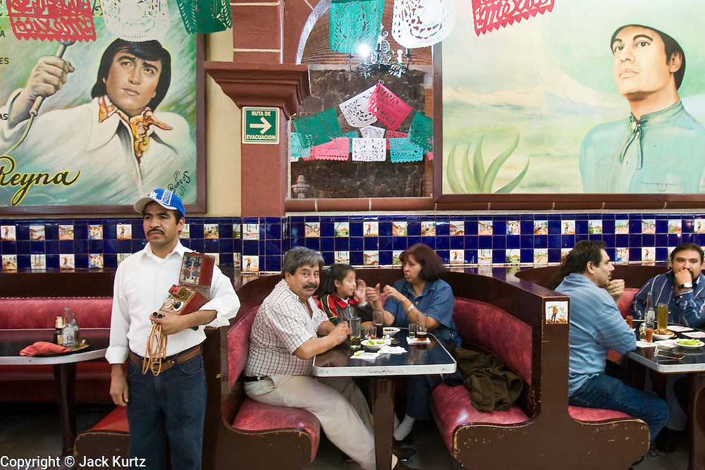 14 SEPTEMBER 2005 - MEXICO CITY: TOMAS ANAYA, right, shocks a group of customers in the Tenampa Bar in Garibaldi Square in Mexico City. Anaya works in the bar shocking customers for $2.00 a jolt five nights a week. Anaya, who inherited the box and his spot in the bar from his father, makes about $80 a week. The activity is called toques in Spanish and is popular in Mariachi bars and traditional Mexican cantinas. PHOTO BY JACK KURTZ