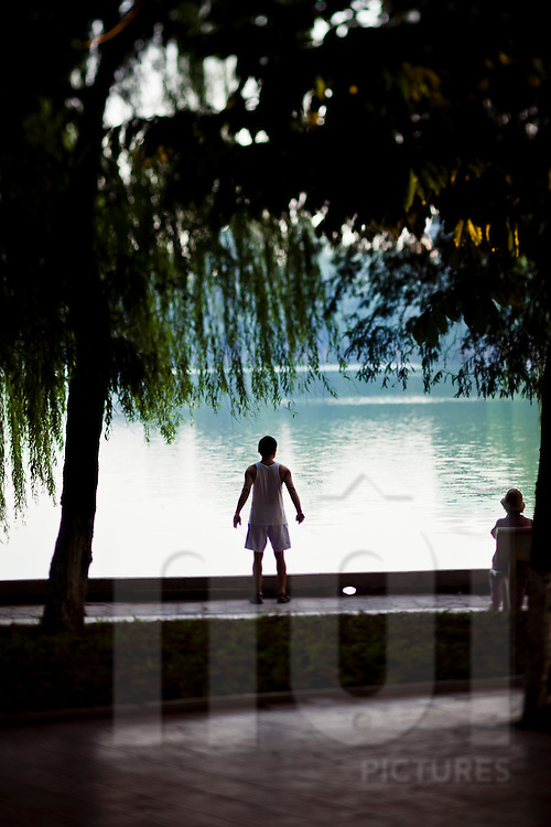 A man performs his morning exercises by Hoan Kiem Lake in downtown Hanoi, Vietnam.