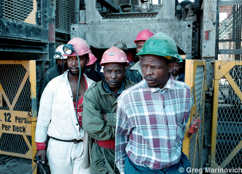 IPMG0388 South Africa, Western Deep, 2000: .Miners exit a lift from their eight hour shift underground working on the gold-bearing ore at Anglo Gold's Savuka mine (formerly Western Deep Levels East) the world's deepest mine May 23, 2000, south-west of Johannesburg, South Africa. .Photograph by Greg Marinovich