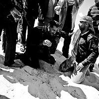 Un combattant rebelle se fait réconforter par ses camarades après avoir été choqué par une explosion d'obus, le 22 mars 2011 à une dizaine de kilomètres d'Aj Dabiya sur la ligne de front.