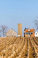A small farmhouse amongst a harvested corn field on the northern Illinois plains.
