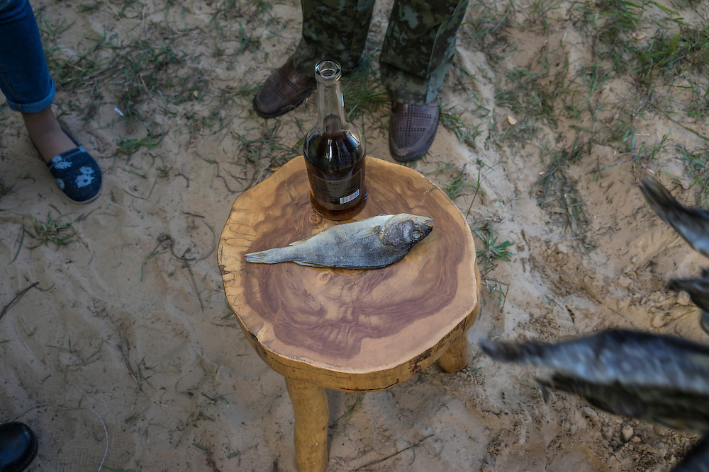Cognac and dried fish are shared during a hunting festival near the Augustów Canal on Saturday, September 17, 2016 in Grodno, Belarus.
