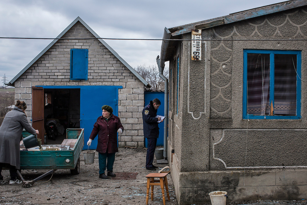 MARIUPOL, UKRAINE - FEBRUARY 5, 2015: A police officer takes a report as local residents clean up debris from shelling overnight which damaged a number of homes in Mariupol, Ukraine. With more than 220 people having died in the past several weeks, a new diplomatic push is underway to bring an end to fighting between pro-Russia rebels and Ukrainian forces. CREDIT: Brendan Hoffman for The New York Times