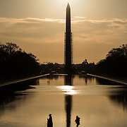 Pedestrians cast their shadows as the early morning sun silhouettes the Washington Monument on the Reflecting Pool in Washington DC. Scaffolding surrounds the Monument part of the way up.