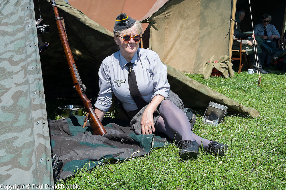 A female re-enactor portrays a Wehrmacht Heferin with the German Army in work uniform blouse shelters from the sun in the shade of a Zeltbahn. Wehrmacht Heferinnen were he German Armed Forces female Auxiliaries. At various periods o time during world war two they were sometimes classified as military personnel other times as uniformed civilians employed by the German Armed Forces (Wehrmacht)<br />  <br /> 04 July 2015<br />  Image &copy; Paul David Drabble <br />  www.pauldaviddrabble.co.uk