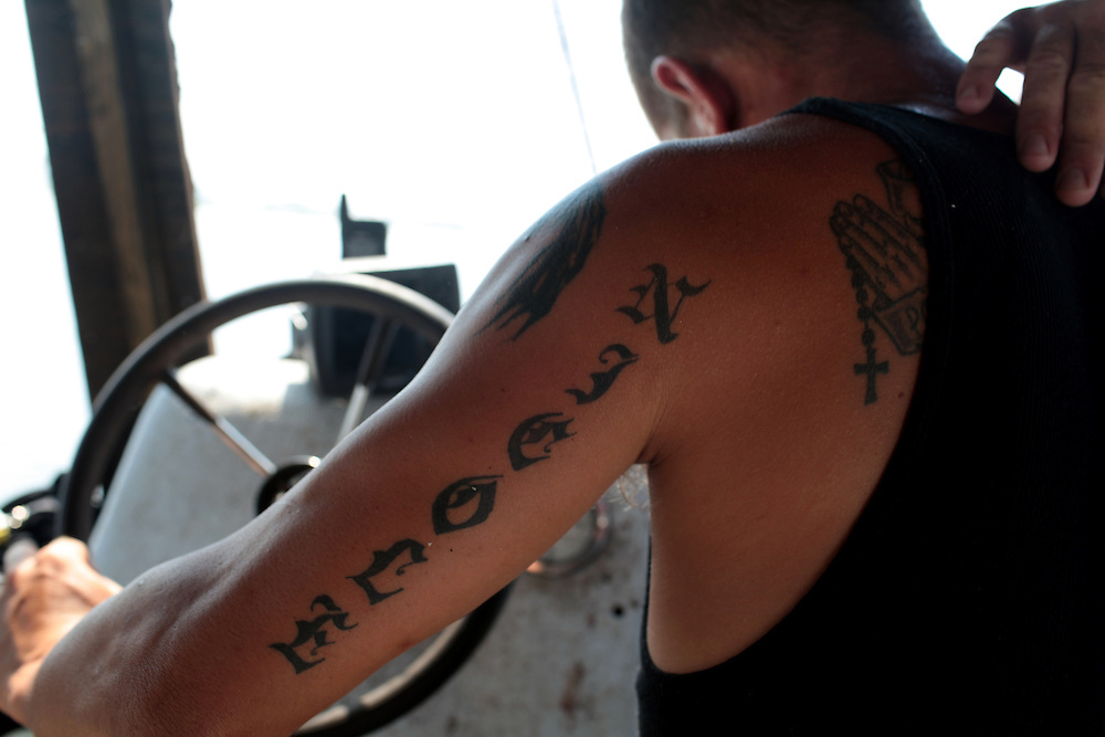 Commercial fisherman Jason Melerine, with his wife's name tattoed on his arm, steers the boat through the bayou in Plaquemines Parish, LA on May 25th, 2010. Local fisherman from St Bernard Parish were desperately fishing the surrounding bayou to earn as much income as possible before authorities shut down the crab fishing while the BP oil spill inched closer.