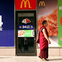 A Buddhist monk walks in front of a McDonald?s restaurant in Kunming, the capital of Yunnan province in China. (Photo/Scott Dalton)