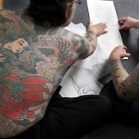 Horiyoshi III (the 3rd) (left of pic), expert Japanese tattooist, examine preliminary skecthes of tattoos with his German understudy Alex Reinke (also known as Horikitsune) (right of pic, with beard), in Horiyoshi's studio in Yokohama, Japan, on Saturday 10th September 2011.