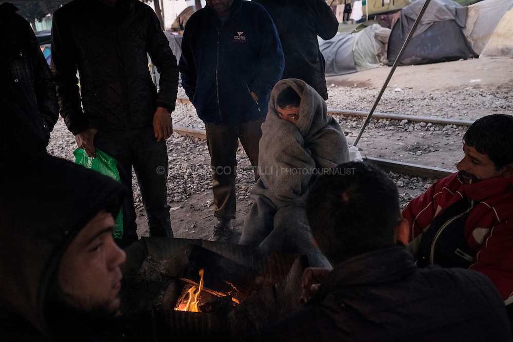 Migrants sit in the cold light of the early morning at Idomeni refugee camp at the Greek border with FYROM (Macedonia).