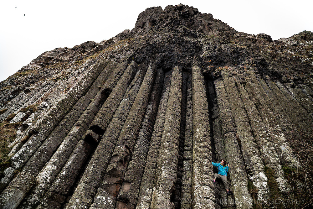 A girl climbs between the columns at the Giant's Causeway. In geological terms these huge columns of basalt make the 'organ pipes', hence this place takes the name of 'The Organ'.